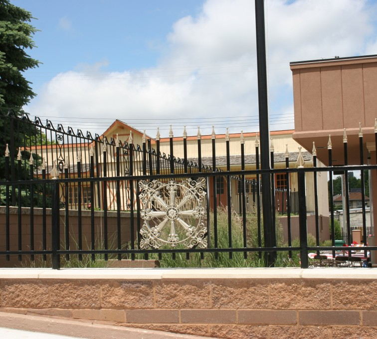 American Fence - Lincoln - Custom Iron Gate Fencing, 1229 Overscallop with quad flare & emblem