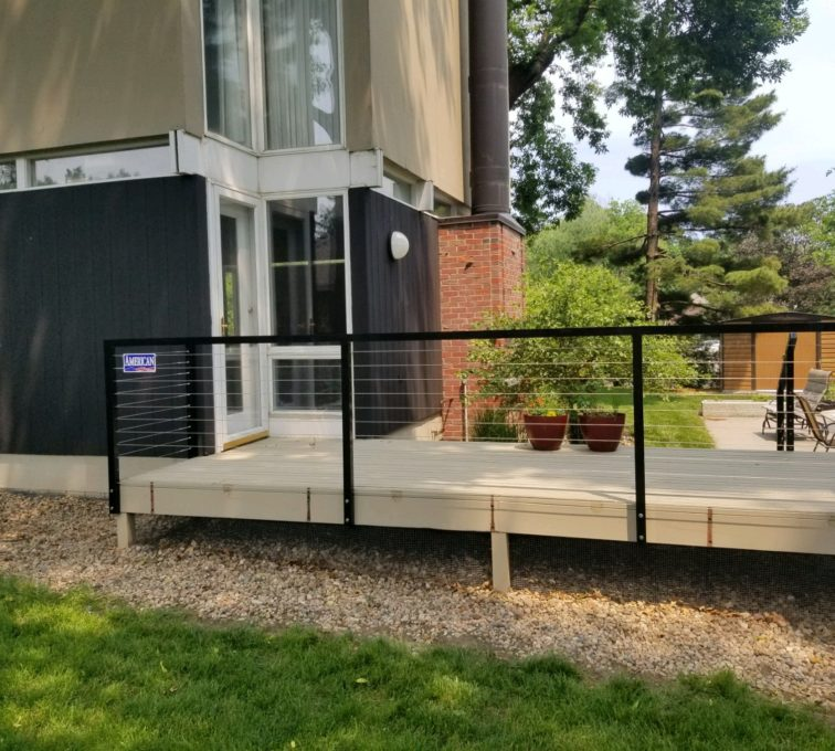 Cable railing installed on a raised platform in a residential backyard