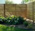 Wooden fence with horizontal pickets that start out really thin at the top and get wider as the fence nears the ground