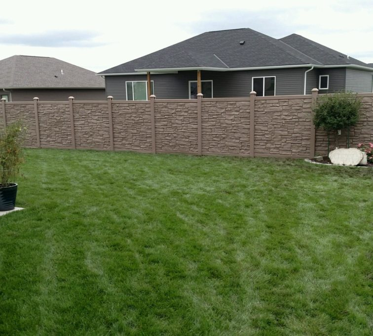 A yard lined with Simtek EcoStone fence