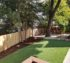 Solid wood privacy fence on one side of the yard, and on the other side there is custom wood rail fencing